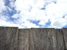 Nuages au delà de vieille barrière en bois Images stock