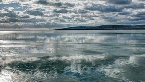 Nuages au-dessus du lac semi-congelé photographie stock