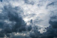 Nuages avec le fond, lumière du soleil par le fond très foncé de nuages des nuages de tempête foncés, fond noir de ciel des nuage Photos stock