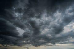 Nuages avec le fond, lumière du soleil par le fond très foncé de nuages du nuage de tempête foncé Photos libres de droits