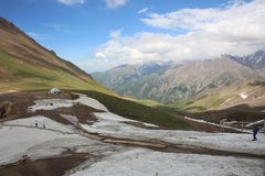 Nuages blancs blancs de ciel bleu de neige d'herbe de vert de montagnes photos stock