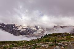nuages blancs denses couvrant la montagne neigeuse photos stock