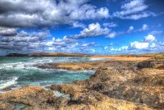 Nuages blancs et ciel bleu Constantine Bay Cornwall England R-U sur la côte du nord cornouaillaise dans HDR coloré images stock