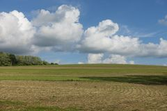 Nuages blancs gonflés au-dessus d'une ferme Hillside images stock
