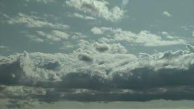 Nuages blancs gonflés se déplaçant à travers le ciel bleu un jour ensoleillé banque de vidéos