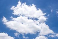 Nuages blancs pelucheux et ciel bleu lumineux Image stock