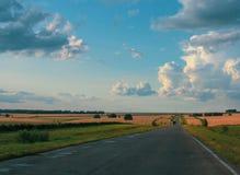 Nuages blancs sur le lansdcape de route et de campagne de ciel bleu photos stock