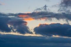 Nuages bleus dramatiques avec un rayon de soleil rouge de coucher du soleil dans le ciel Photo libre de droits