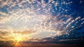 Nuages bouclés dans les rayons du soleil Photographie stock libre de droits