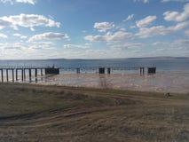 Nuages, ciel bleu, rivière, rivage, dock, l'eau, endroit du ` s de pêcheur, construction de fer, industrie, cargaisons, bateaux Photo libre de droits