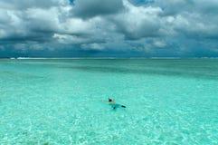 Nuages d'obscurité des Maldives d'océan d'homme de natation Image stock