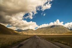 Nuages dans le ciel sur la route à Castelluccio, Italie Photos stock