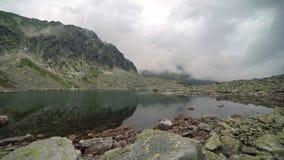 Nuages dans le lac de montagnes banque de vidéos