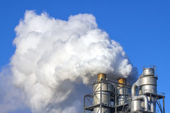 Nuages de fumée d'une cheminée contre le ciel bleu Photographie stock
