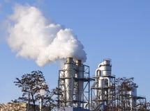 Nuages de fumée d'une cheminée contre le ciel bleu Images libres de droits