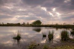Nuages de laps de temps se déplaçant au-dessus d'un lac Photos stock