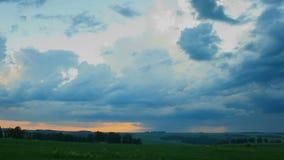 Nuages de pluie mobiles au-dessus de champ un coucher du soleil, laps de temps banque de vidéos