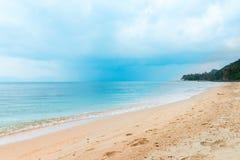 Nuages de pluie tropicaux sur la mer calme et la plage abandonnée Photographie stock