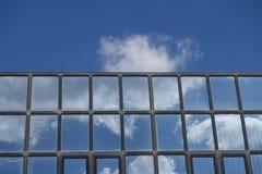 Nuages de réflexions et ciel bleu sur des fenêtres de bâtiment photographie stock libre de droits