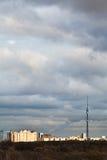Nuages de soirée au-dessus des maisons et de la tour de TV Images stock