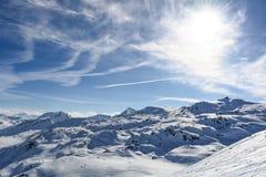 Nuages de soleil de montagne de neige avec le temps ensoleillé photos stock