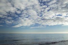 Nuages de stratocumulus au-dessus des vagues bleues d'eau de mer Image stock