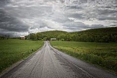 Nuages de tempête au-dessus d'une route dans le domaine herbeux Images stock
