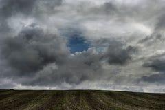 Nuages de tempête au-dessus du champ brun Photos stock