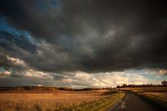 Nuages de tempête foncés au-dessus de pré de montagne au coucher du soleil Photo stock