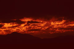 Nuages de tempête foncés avec la lumière rouge Image stock