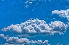 Nuages drôles sur le ciel bleu Photographie stock libre de droits