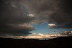 Nuages dramatiques au-dessus d'un champ foncé Photos libres de droits