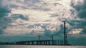 Nuages dramatiques au-dessus d'un pont en construction clips vidéos