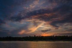 Nuages dramatiques au-dessus de l'eau pendant le coucher du soleil photographie stock libre de droits
