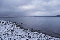 Nuages dramatiques au-dessus de scène de lac d'hiver avec le rivage neigeux Photos stock