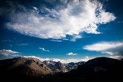 Nuages dramatiques au-dessus des montagnes couvertes par neige Photographie stock
