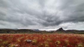 Nuages dramatiques au-dessus des montagnes de l'Islande et de laps de temps rouge de pré banque de vidéos
