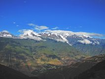 Nuages en ciel bleu au-dessus des montagnes neigeuses images stock