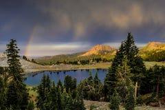 Nuages et arc-en-ciel de pluie au-dessus de lac Hélène, parc national volcanique de Lassen Images libres de droits