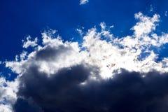 Nuages et lumière denses contre le ciel bleu Photos stock