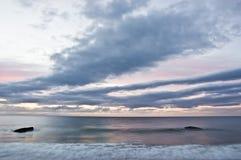 Nuages et mer rapides au lever de soleil avec des soutes de la défense WW2 Images stock