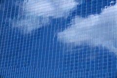 Nuages et réflexion de ciel bleu dans le verre du gratte-ciel Images stock