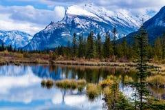 Nuages et soleil de tempête essayant de faire une pointe au-dessus des lacs vermeils Images libres de droits