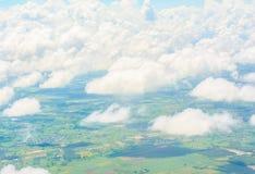 Nuages et vue de terre de la fenêtre d'un avion Photographie stock libre de droits