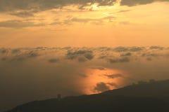 Nuages flottant au-dessus de la mer sur un coucher du soleil Photo libre de droits