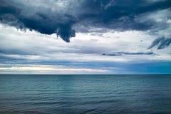 Nuages foncés au-dessus de mer Images stock