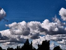 Nuages foncés et ciel bleu photographie stock
