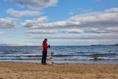 Nuages foncés recueillant au-dessus du lac Baïkal Une fille et un chien marchent le long de la côte photographie stock