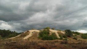 Nuages gris au-dessus de dune de sable Photographie stock