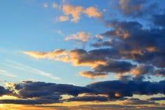nuages Gris-bleus illuminés par lumière du soleil jaune contre le ciel bleu un jour photo stock